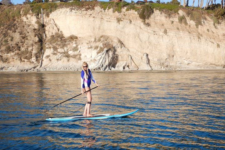 Girl in purple swimsuit on stand up paddle board