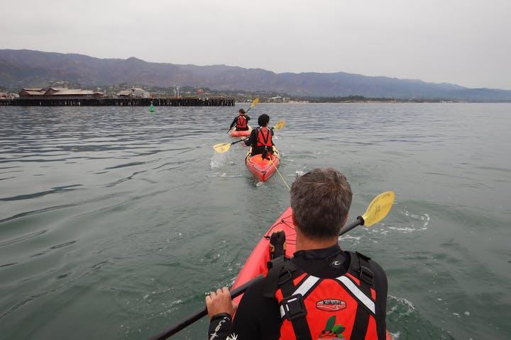 People kayaking out into the ocean in orange kayaks