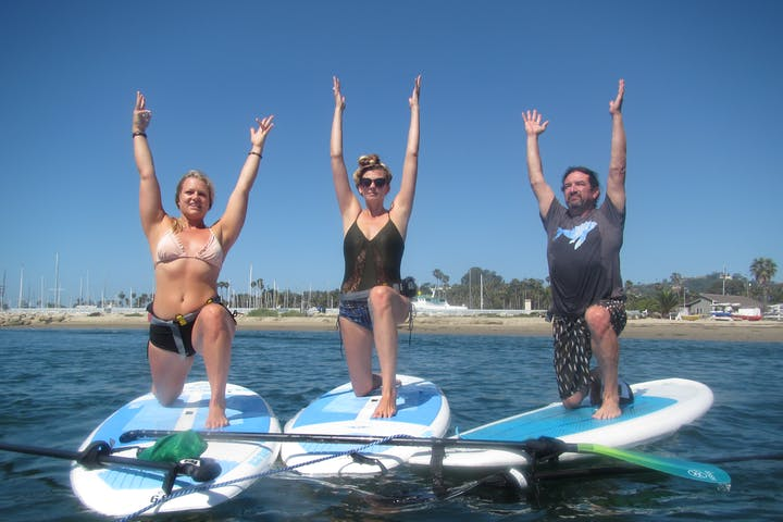 3 people doing yoga on stand up paddle boards