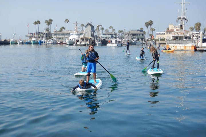 group of kids on stand up paddle boards