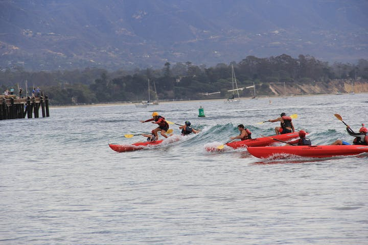 Group of kayakers paddling on waves near shore