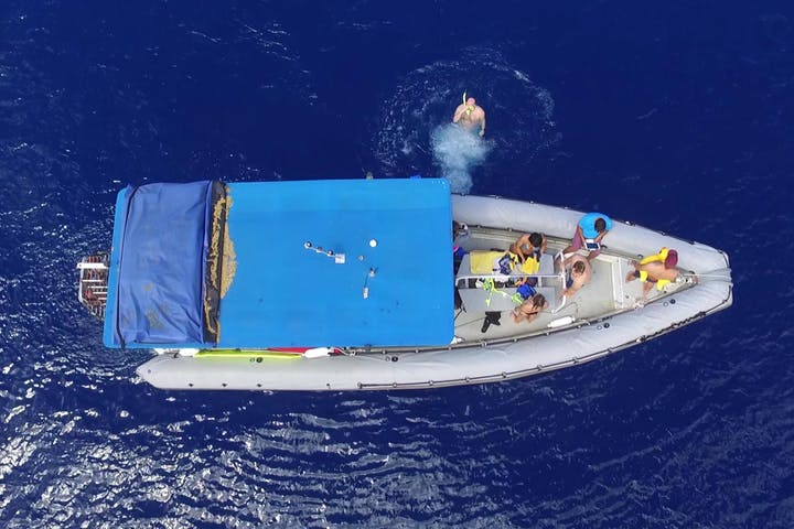 overhead shot of boat with people jumping off