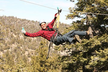 Man giving thumbs=up on zip-line
