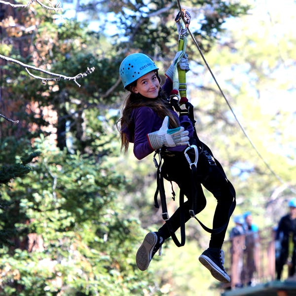 Small girl looking back while zip-lining