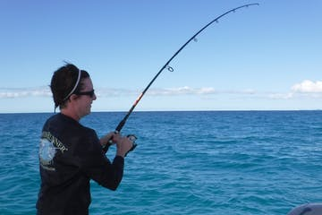 woman reeling in fish on a boat