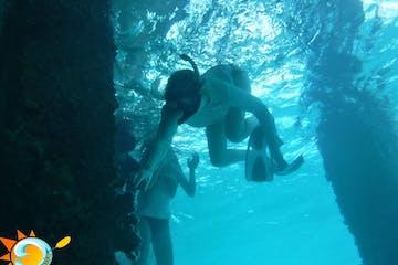 Boy snorkeling underwater near a pier