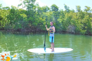 Man standing on paddleboard making the hang loose sign with his free hand