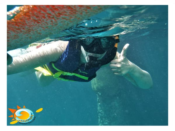 girl snorkeling giving thumbs up