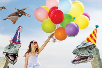 Young girl holding a balloons with dinosaur in a background