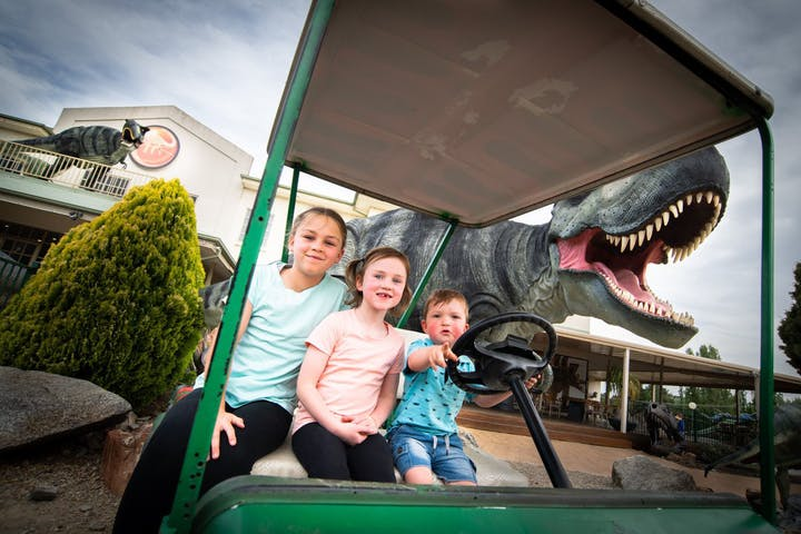 Three kids riding card with dinosaur in a background