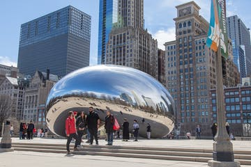 a group of people standing in front of Millennium Park