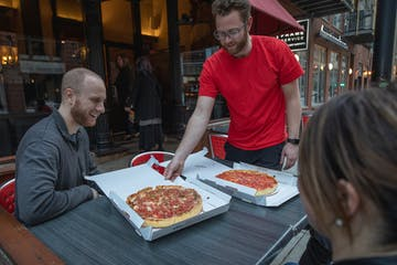 a man and a woman cutting a pizza