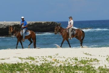 Two people riding horses on the beach in Aruba