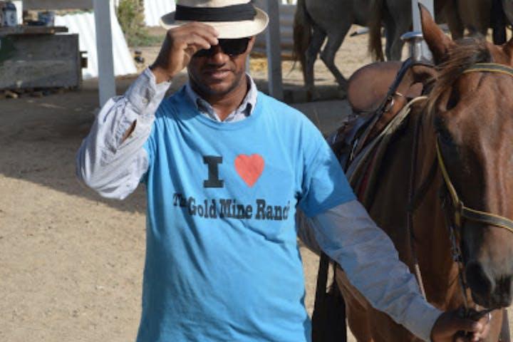 Man in hat walking horse