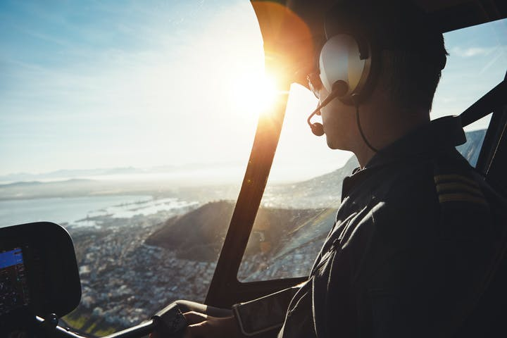 a helicopter pilot flying aircraft over a city on a sunny day