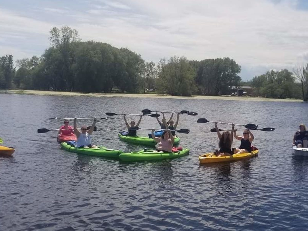 a group of people rowing a boat in a body of water