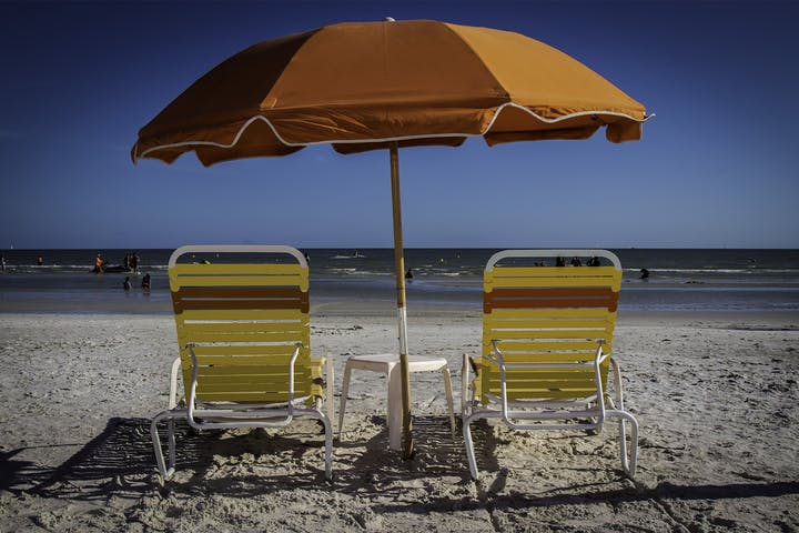two beach chairs and an umbrella facing the surf