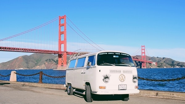 Vintage white van driving up to the Golden Gate Bridge
