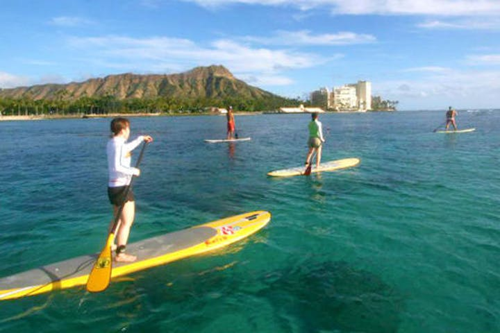 group stand up paddleboarding in water