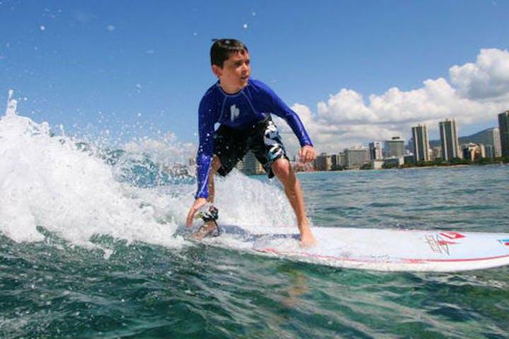 little boy surfing on wave