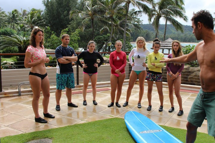 group learning how to surf on land with instructor