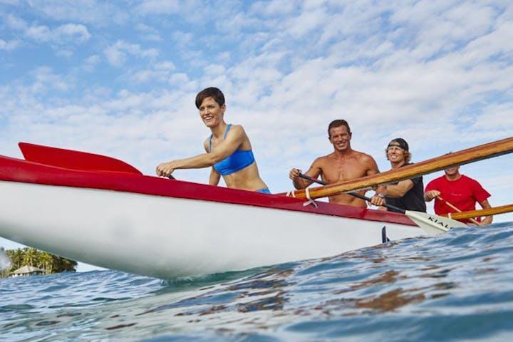 people rowing in kayak smiling on water