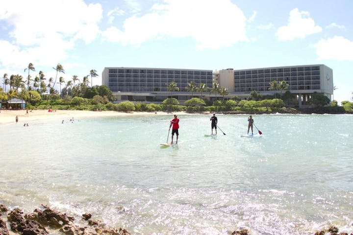 group stand up paddleboarding on water