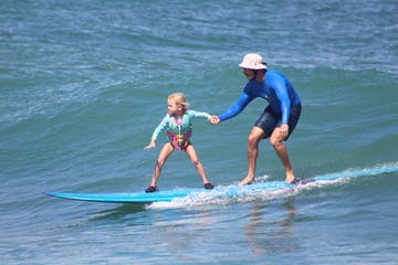 little girl surfing with instructor