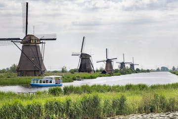 Five windmills in a row and a boat on a river