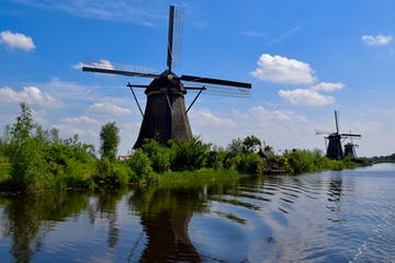 Four windmills next to a river