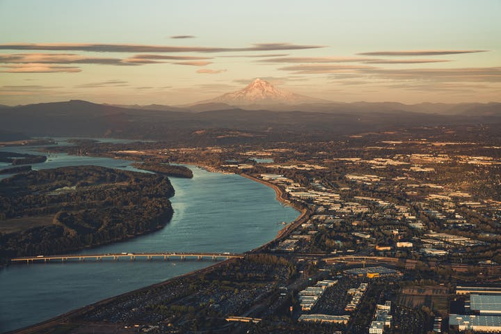 Aerial view of Portland with Willamette flowing through it and Mount Hood in the distance