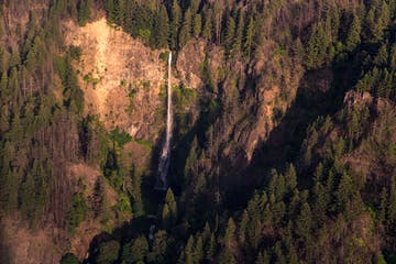 Aerial view of tall rushing waterfalls cascading over cliff