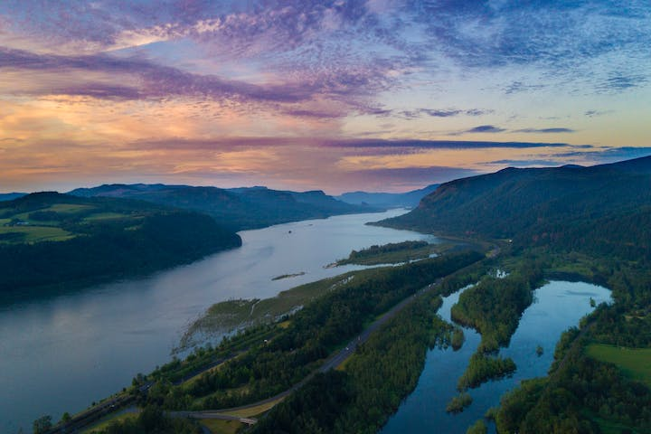 Aerial view of long lake surrounded by forests during a multi-colored sunset