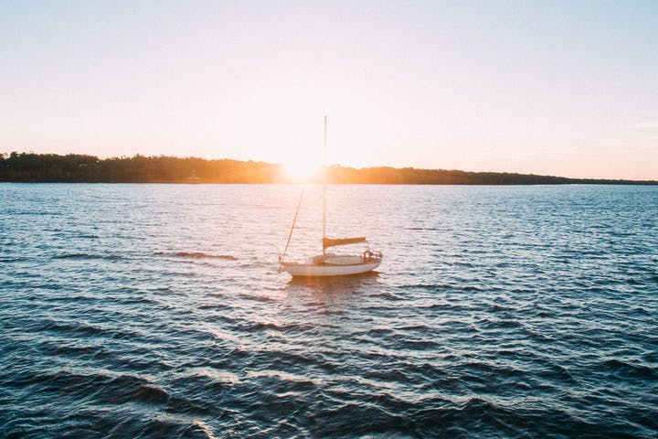 White boat sailing on a sunset