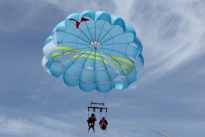 Two women parasailing with light blue sail