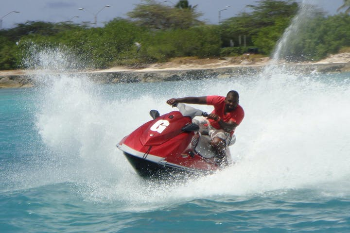 Man in red shirt on red jet ski with big splash