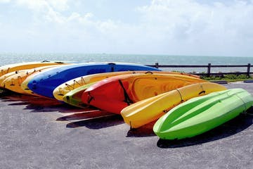 A dozen multicolor kayaks lying in a parking lot with the ocean in the background