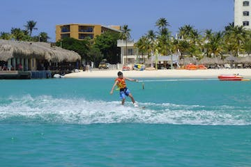 Boy in orange life jacket & blue swim trunks wakingboarding with hotels & cabanas on the beach are in the background.