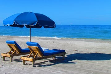 Two blue lounge chairs with a matching blue sun umbrella sit on the beach facing the ocean