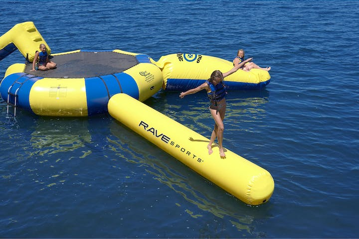 A Water trampoline floating in water with 3 girls playing on it