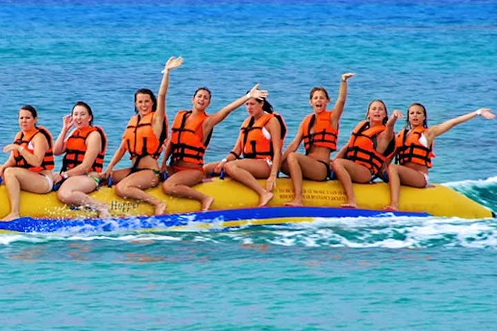 Eight girls in orange life jackets sitting on a banana boat (a long floating raft shaped like a banana)
