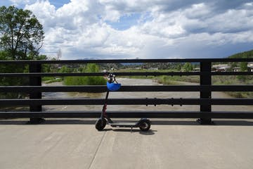 Scooter on bridge with town in background