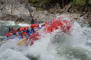 whitewater rafting group battling intense rapids on half day trip