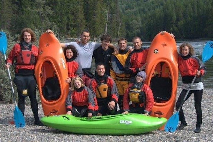 Group of beginner whitewater kayak students taking group photo with gear on river's edge