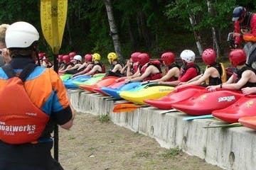 long row of intermediate kayakers sitting on the beach listening to instructors