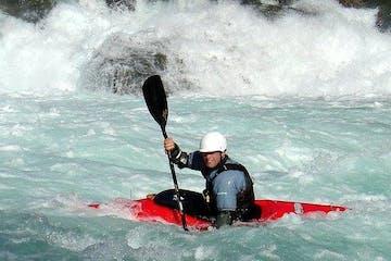 whitewater kayaker battling through intense rapid