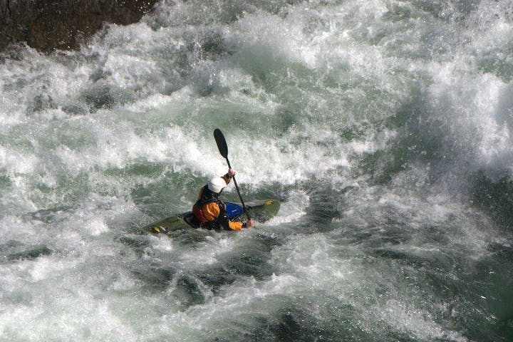 whitewater kayaker fighting through large rapids