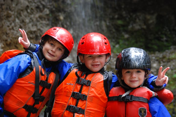 Three children in helmets and life jackets