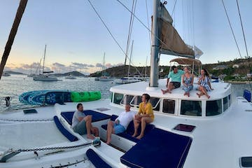 Panorama of people sitting on front of catamaran during sunset in the harbor