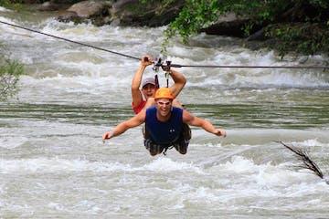 Men ziplining over river